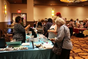 Organizer Darlene Montague, left, assists a few of the many customers who bought from her Origami Owl booth at the first Simple Indulgence event held on Nov. 5. Photo by Stephanie Clark.