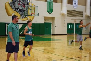 Bulldog coach Sean FitzSimons looks over tryouts Saturday morning Nov. 12. Two players FitzSimons is counting on left to right are point guard Jarrett Tietjen and returning lreading score Andrew Memmott bring up the ball during the Bulldogs workout.