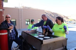 With the supervision of Deputy Fire Chief Rick Resnick, left, who claimed to be near the grill for heating purposes, members of the CERT team cooked for nearly 40 guests at the 4th annual Breakfast with Santa event held for families of emergency responders. Photo by Stephanie Clark.